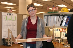 Madison holds the prototype of a manifold caliper she created on the job at Caterpillar.